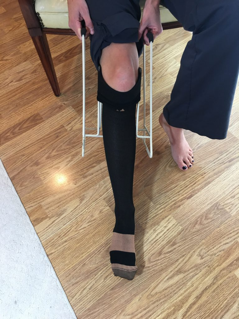Put on compression socks - pull compression sock all the way using donning tool