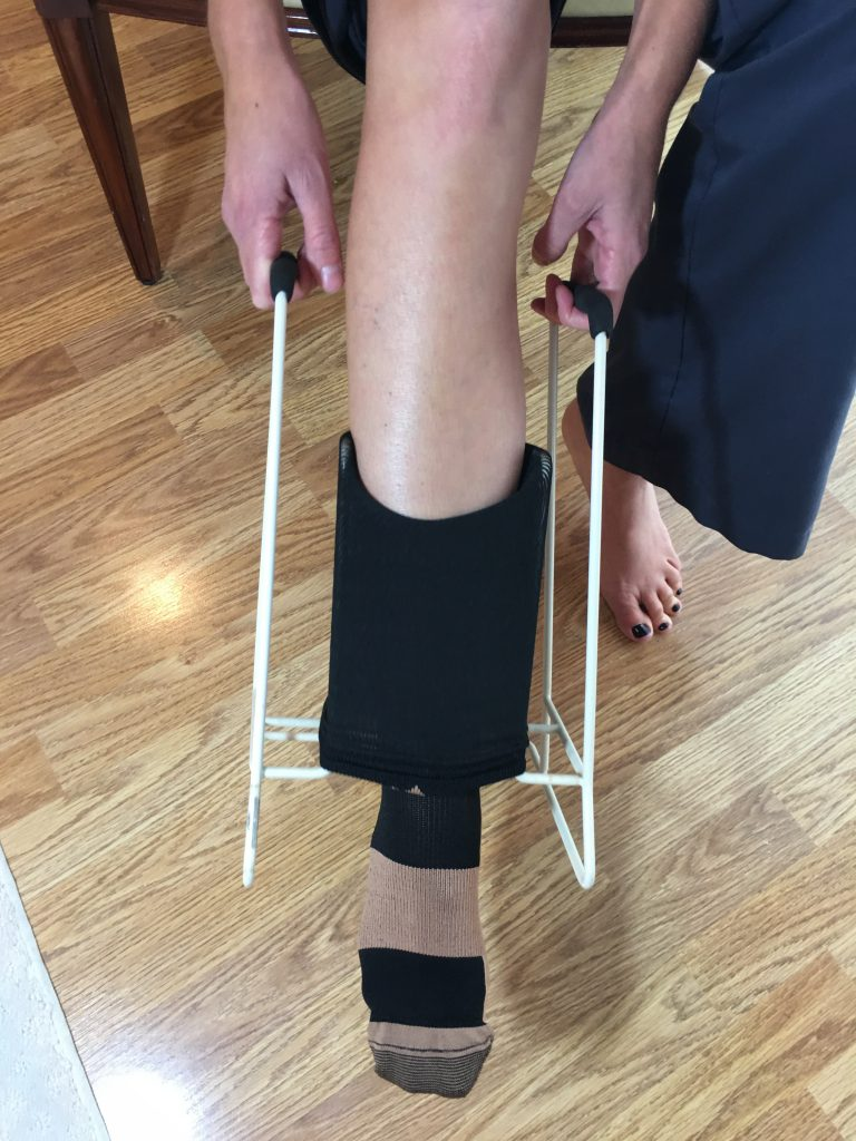 Put on compression socks - pull compression sock over leg using donning tool