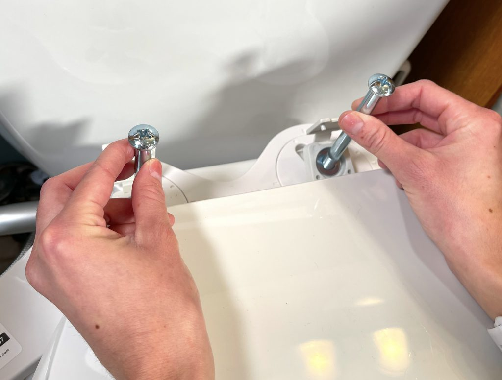 Slide toilet seat mounting bolts through the mounting holes