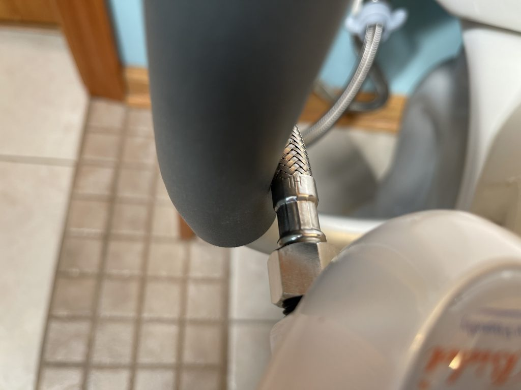 Water line from bidet interfering with arms on raised toilet seat