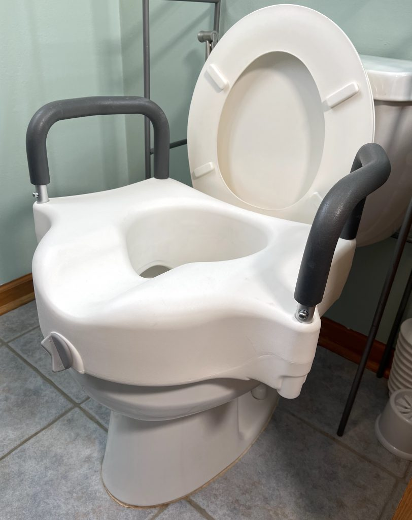 Clamp-on raised toilet seat front of riser placed into position inside bowl