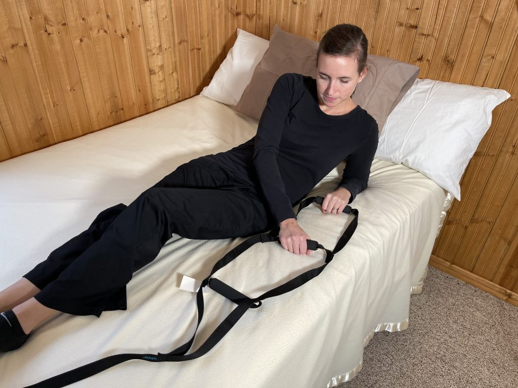 Bed ladder installed at the foot of bed with person using it - Bed Mobility Aid